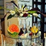 Masa sampanie intrare Motel Bucium decorata cu orhidee alba, cafea, aranjamente floral cale lalele, sculpturi fructe