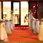 Decor intrare Casa Vanatorului covor rosu stalpi cu aranjamente florale alb-rosu hortensii trandafiri miniroze eustoma frezii Unique Moments